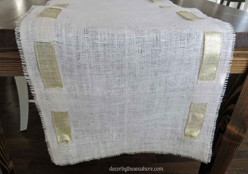 DIY Burlap Table Runner- This burlap table runner is so pretty and perfect for any holiday! Get the full tutorial here!   decorbytheseashore.com