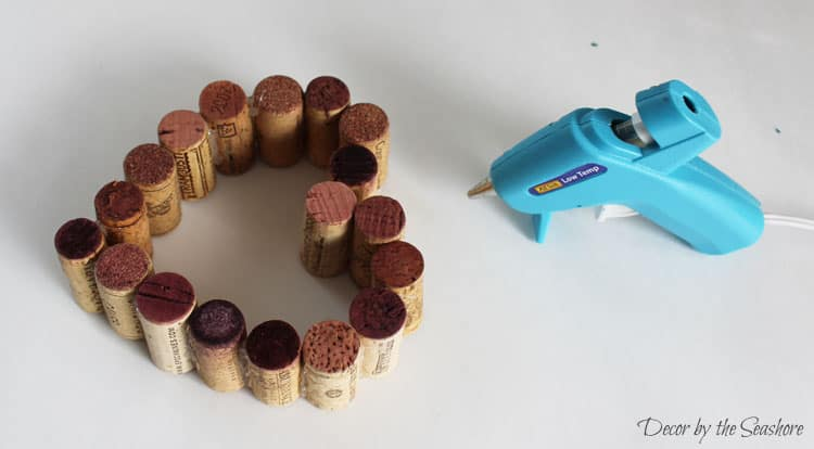 How cute is this Valentine's Day wine cork heart decoration? It's super simple to make and would look fabulous on a mantel or as a table centerpiece. You could even give it as a gift for a wedding, anniversary, or just because! | decorbytheseashore.com