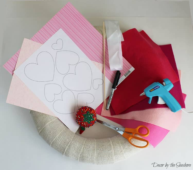 This DIY Valentine's Day burlap wreath is so cute! It's an interchangeable wreath, so you can swap out the accessories every holiday without buying a new wreath! It even includes a free printable heart template for Valentine's Day crafts and projects! | decorbytheseashore.com