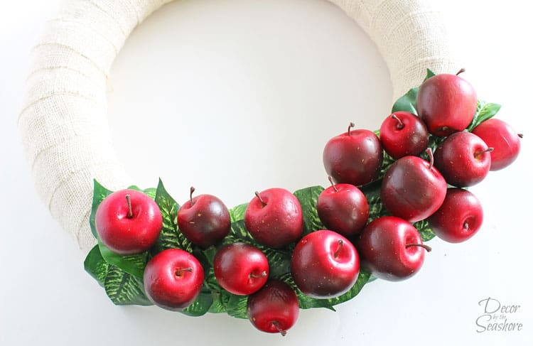 This super cute fall apple wreath is so easy to make! It's the perfect DIY addition to your fall decor! Best of all, it's interchangeable, so when the season's over, you can take everything off and reuse the wreath form! Too easy! | decorbytheseashore.com