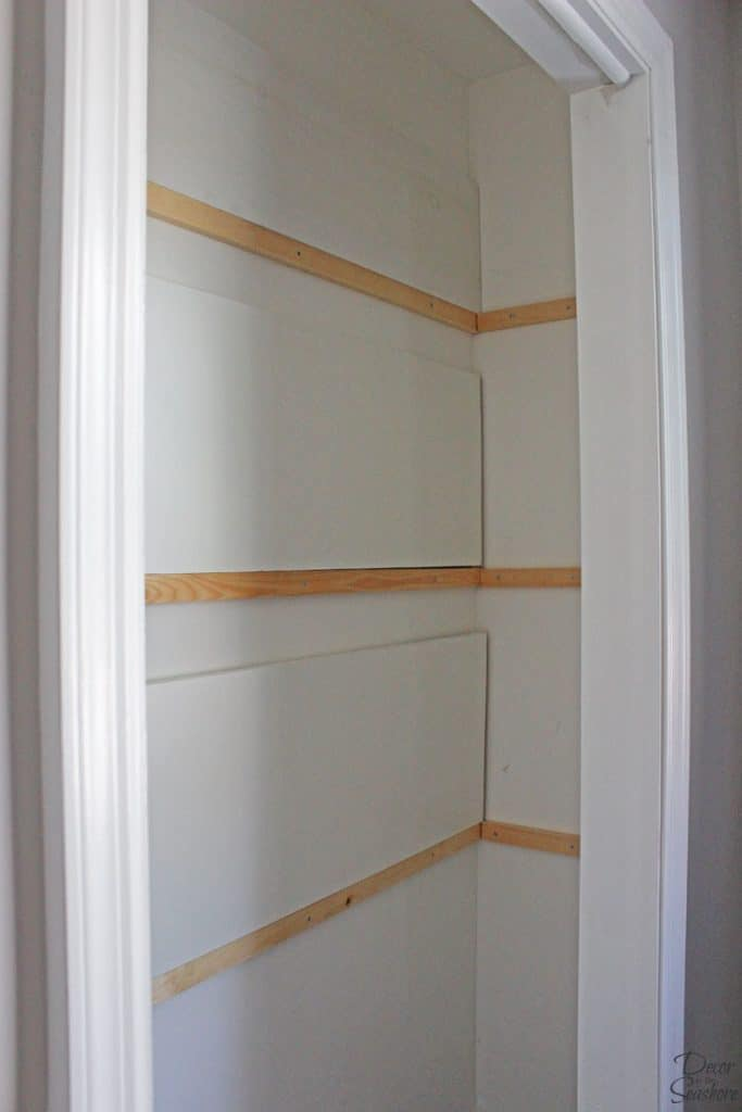 In need of more closet storage? This easy tutorial shows you how to make custom closet shelves on a budget! These DIY shelves are the perfect way to add storage space and get your closet organized once and for all! | decorbytheseashore.com