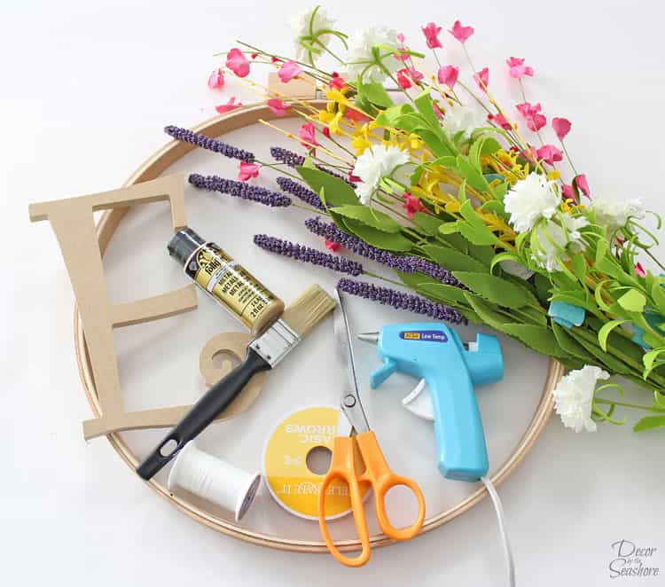 This DIY monogram embroidery hoop wreath is so elegant and beautiful! Just gather a few supplies and follow the easy instructions to make your own! This floral wreath is the perfect piece of DIY home decor to display in your home!   decorbytheseashore.com